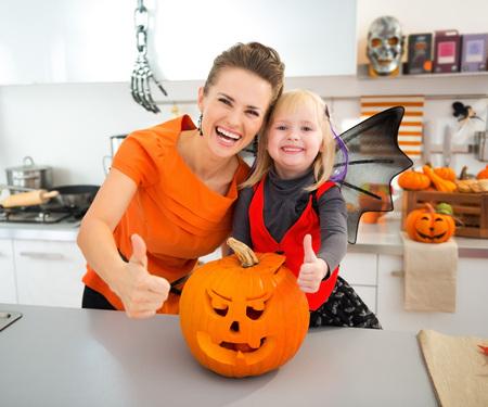 Lachend halloween gekleed meisje met moeder die zich in ingerichte keuken bij grote oranje pompoen Jack-O-Lantern en tonen duimen omhoog. Traditionele herfstvakantie