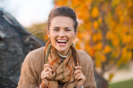 laughing: Portrait of young laughing brunette woman relaxing in beautiful evening in autumn park Stock Photo