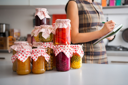 autumn food: In the foreground, a stack of glass jars filled with home-made preserved vegetables. In the background, the profile of a woman listing the different ingredients before she stores them away for winter.