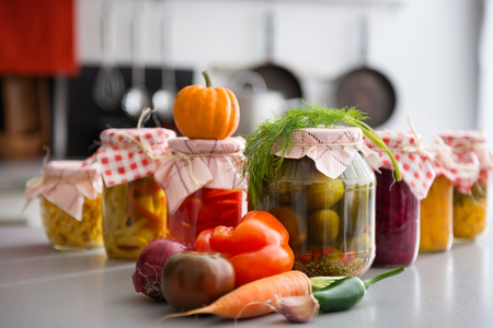 autumn food: Oh, the tasty, crunchy treats that people will be feasting on in the winter, thanks to all of these preserved and pickled vegetables in glass jars. On the kitchen counter, fresh seasonal vegetables.
