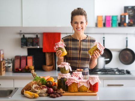Holding up two jars of preserved vegetables, this happy, elegant woman is proud of all she has accomplished in preserving fresh vegetables. How tasty the winter months will be...