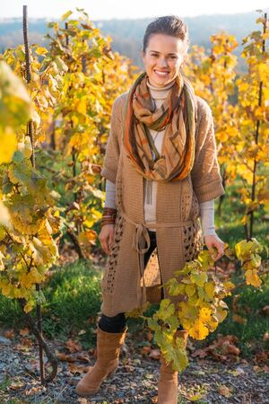 grape field: Full length portrait of smiling brunette woman winegrower standing in autumn grape field. Small business concept