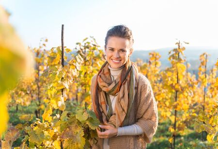 grape field: Smiling young brunette woman winegrower standing in autumn grape field. Small business concept