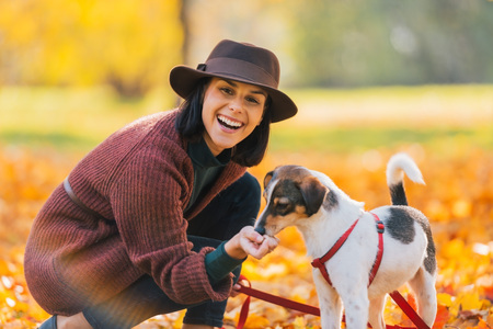 Portrait of young woman in brown hat feeding dog in autumn park Stock Photo