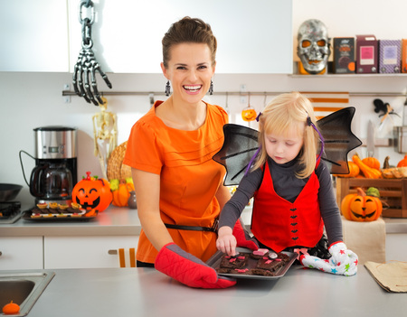 mam: Blond girl in bat costume with smiling mother in decorated kitchen holding tray with homemade Halloween biscuits for Trick or Treat. Ready to halloween party. Traditional autumn holiday