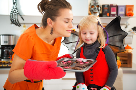 treating: Blond girl in bat costume with young mother enjoying the aroma of freshly baked Halloween biscuits for Trick or Treat. Ready to halloween party. Traditional autumn holiday
