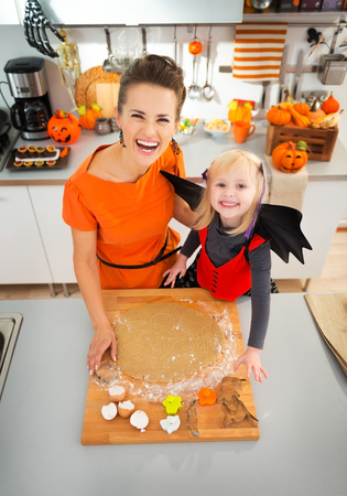 pastry cutter: Happy young mother with daughter in bat costume cutting out Halloween cookies with pastry cutter from rolled pastry in decorated kitchen. Traditional autumn holiday