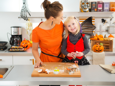 pastry cutter: Happy halloween dressed girl with young mother in decorated kitchen cutting out cookies with pastry cutter from rolled pastry. Traditional autumn holiday Stock Photo