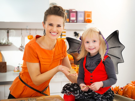 treating: Smiling blond girl in bat costume with mother holding uncooked Halloween cookies in decorated kitchen. Halloween treats ready to go into oven. Traditional autumn holiday.