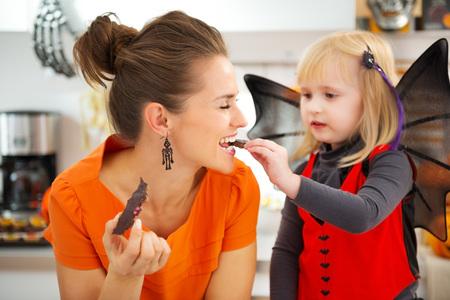 familia comiendo: Muchacha rubia en traje de murciélago con la madre feliz en la cocina decorada comer galletas de Halloween recién hechas en casa para Trick or Treat. Fiesta tradicional de otoño