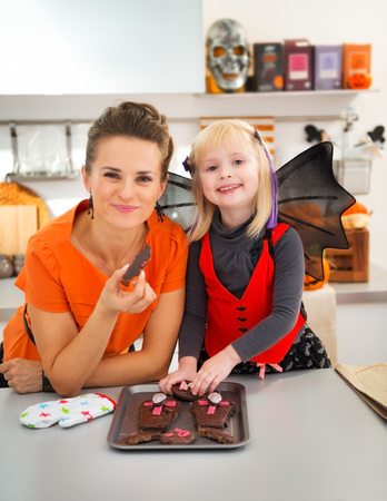 mam: Portrait of smiling mother and girl in bat costume in kitchen showing off freshly baked Halloween biscuits for Trick or Treat. Ready to halloween party. Traditional autumn holiday