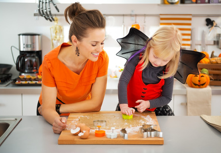 trick or treating: Halloween dressed girl with young mother in decorated kitchen cutting out cookies with pastry cutter from rolled pastry. Traditional autumn holiday Stock Photo