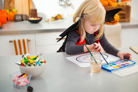 enthusiastically: Interested halloween dressed blond little girl enthusiastically drawing on paper with paints pumpkin Jack-O-Lantern in decorated kitchen. Traditional autumn holiday