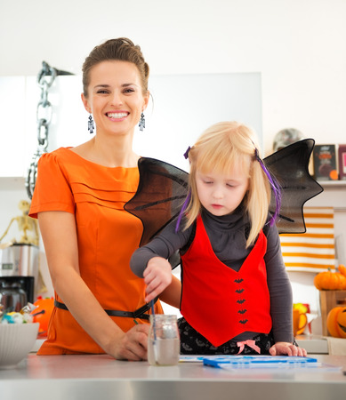 holiday spending: Preparation for a party is in full swing. Little blond girl in halloween bat costume spending time with mother in decorated kitchen. Traditional autumn holiday