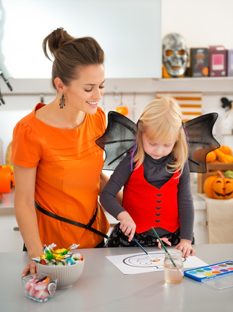 Smiling mother with halloween dressed blond little girl drawing on paper with paints orange pumpkin Jack-O-Lantern in decorated kitchen. Traditional autumn holiday