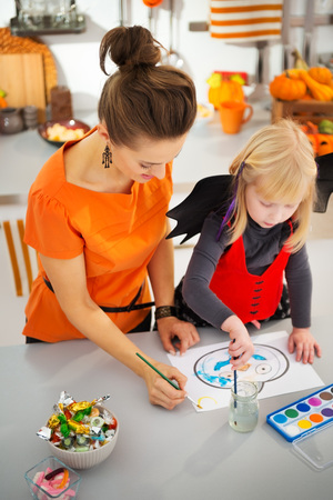 holiday spending: Blond little girl in halloween bat costume with mother drawing on paper with paints original blue pumpkin Jack-O-Lantern in decorated kitchen. Traditional autumn holiday Stock Photo