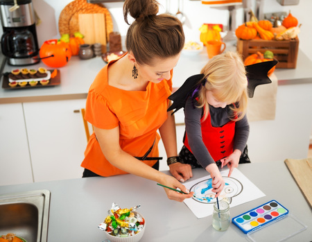 Halloween dressed blond girl with mother drawing on paper with paints pretty creative blue pumpkin Jack-O-Lantern in decorated kitchen. Traditional autumn holiday Banco de Imagens