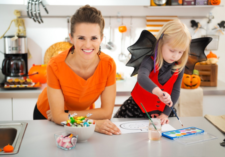 Happy mother with daughter in halloween bat costume drawing on paper with paints orange pumpkin Jack-O-Lantern.  Decorated kitchen. Traditional autumn holiday