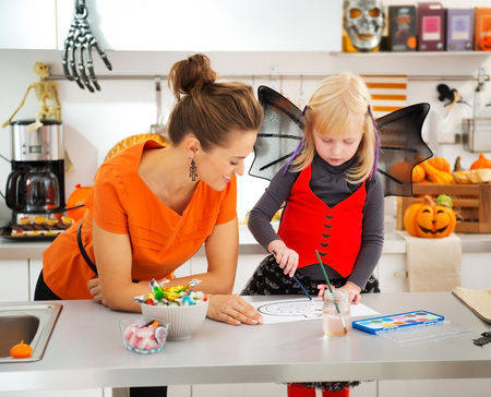 Halloween dressed blond girl with young mother drawing on paper with paints orange pumpkin Jack-O-Lantern in decorated kitchen. Traditional autumn holiday Banco de Imagens