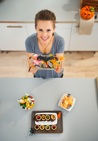 Kids will be stunned! Smiling woman in kitchen showing horribly tasty delicious treats for halloween party. Traditional autumn holiday