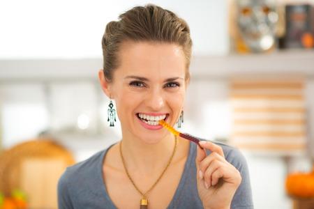 キャンディ グミのワームを食べて笑顔の若い女性。ハロウィーンのキャンディはとても良いです!伝統的な秋の休日。