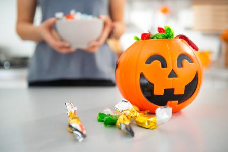 クローズ アップ ハロウィン ジャック-o-ランタン バケット トリックの完全またはバック グラウンドでお菓子と料理とお菓子の女性を扱います。ハ 写真素材
