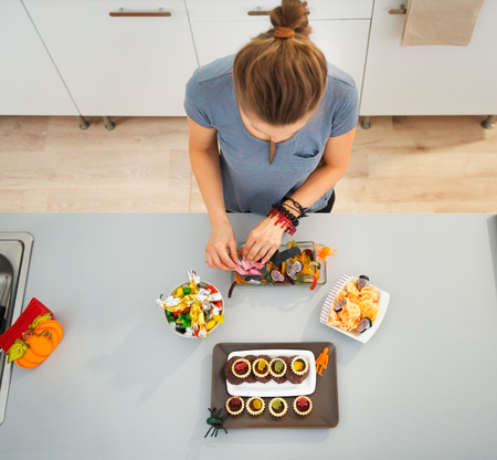 Woman in kitchen preparing horribly tasty treats for halloween party. Ready to halloween party! Traditional autumn holiday Stock Photo