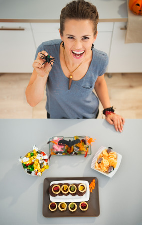 horribly: Kids will be stunned! Smiling woman in kitchen with spider toy in hand preparing horribly tasty delicious halloween treats for kids party. Traditional autumn holiday