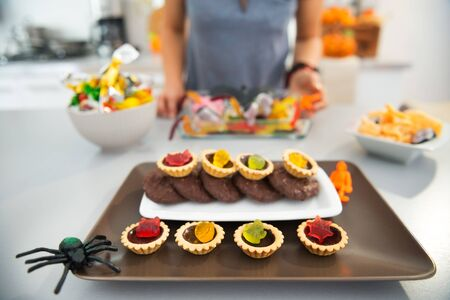 horribly: Closeup on horribly tasty delicious halloween treats on table in kitchen and woman in background. Ready to halloween party. Traditional autumn holiday Stock Photo