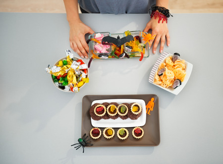 horribly: Kids will be stunned! Closeup on woman in kitchen preparing horribly tasty delicious halloween treats for kids party. Traditional autumn holiday Stock Photo