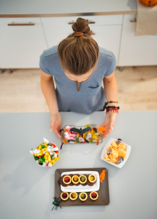 horribly: Woman in kitchen preparing horribly tasty halloween trick or treat for kids party. Ready to halloween party! Traditional autumn holiday Stock Photo