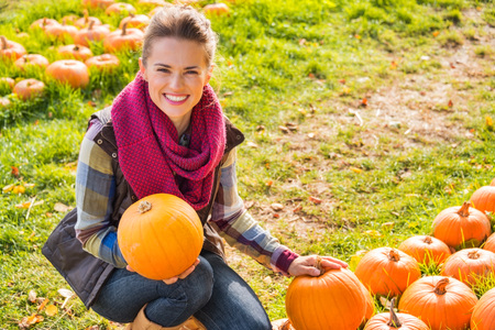 Portrait of smiling beautiful woman holding pumpkins on the pumpkin patch on farm during the autumn season 版權商用圖片