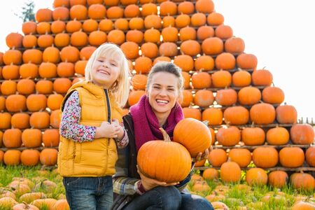 happy life: A beautiful smiling woman and cute little girl holding pumpkins in front of big pile of orange pumpkins in autumn outdoors