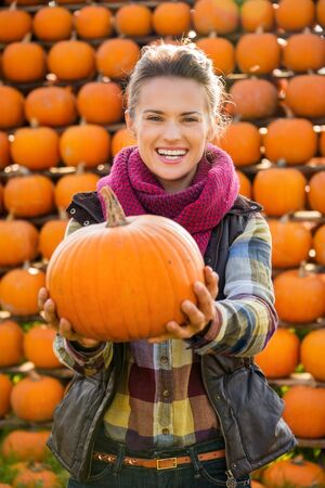 dynia: Portrait of smiling young woman holding big pumpkin on farm during the autumn season