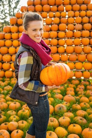 happy life: Portrait of beautiful smiling woman holding pumpkin in front of pumpkin rows on farm during the autumn season Stock Photo