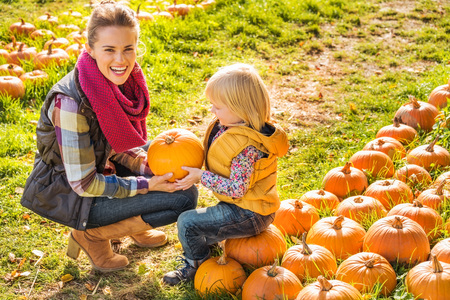 happy life: Beautiful smiling woman and child choosing a pumpkin on a pumpkin patch on farm during the autumn season