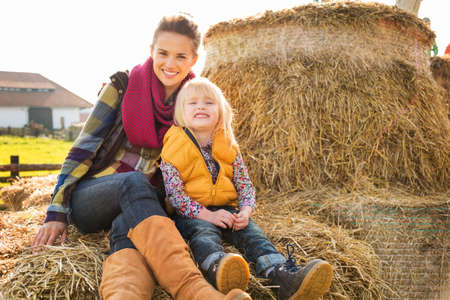 Portrait of happy woman with cute child sitting on the hay on farm on sunny autumn day