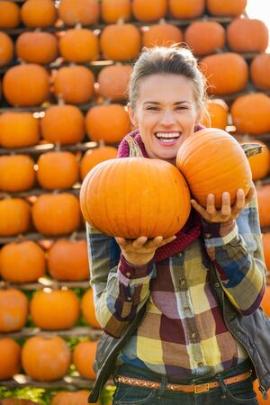 happy life: Portrait of young smiling beautiful woman holding pumpkins in front of big pyramid of pumpkins on farm during the autumn season
