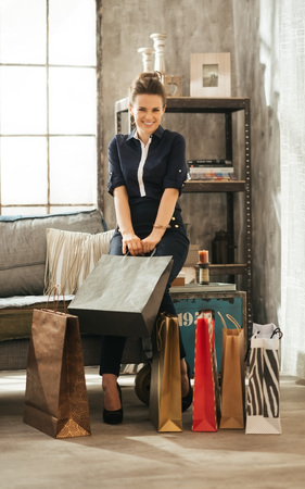 house shopping: Care-free and elegant brown-haired woman with colourful shopping bags sitting on divan in stylish loft apartment. Good shopping spree makes any woman happy. Luxurious life concept