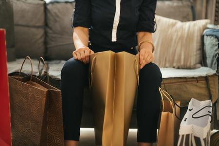 divan: Cierre en elegante mujer sentada en el diván con bolsas de compras en el apartamento tipo loft y comprobar nuevas purchasings. Lujoso concepto de vida Foto de archivo