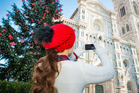 hristmas: Seen from behind, woman tourist in cozy warm outfit taking photo of Duomo in сhristmas decorated historical center of Florence, Italy.