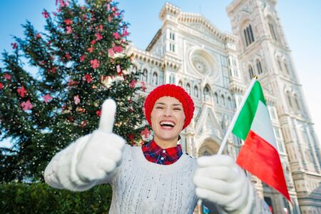 christmas spending: Thumbs up for Christmas in Florence! Happy traveler woman with italian flag standing in front of traditional christmas tree near Duomo while spending fun time in Florence, Italy