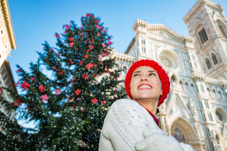 opening up: Happy young woman in white sweater standing in front of traditional christmas tree near Duomo in Florence, Italy. She inspired by opportunities opening up in New Year. Christmas and travel concept.