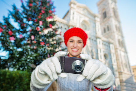 hristmas: Close up on camera in hands of woman tourist taking a photo in сhristmas decorated historical center of Florence, Italy. Christmas and travel concept.