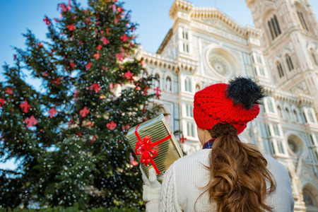 anonym: Seen from behind, woman tourist in red knitted hat holding present gift box while standing near large Christmas tree in Florences historic center. Christmas and travel concept.