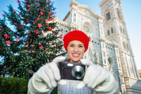 hristmas: Playfully taking a photo, a woman tourist in red knitted hat laughs as she aims her camera to take a photo, Italy. In the background, сhristmas decorated historical center of Florence.