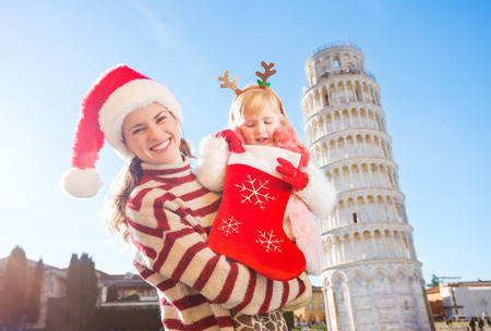 christmas spending: Mother in Christmas hat holding daughter in funny reindeer antlers looking into Christmas sock for a gift. Leaning Tour of Pisa in background. They spending exciting Christmas time traveling Italy