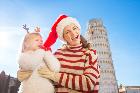 christmas spending: Girl wearing funny reindeer antlers pulling Christmas hat from head of her smiling mother in front of Leaning Tour of Pisa, Italy. They spending exciting Christmas time traveling.