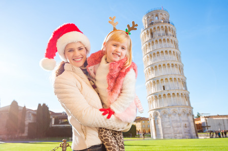 christmas spending: Portrait of happy mother in Christmas hat and daughter wearing funny reindeer antlers standing in front of Leaning Tour of Pisa, Italy. They spending exciting Christmas time traveling.