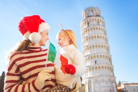 christmas spending: Happy mother in Christmas hat and daughter wearing funny reindeer antlers holding Italian flag in front of Leaning Tour of Pisa, Italy. They spending exciting Christmas time traveling.